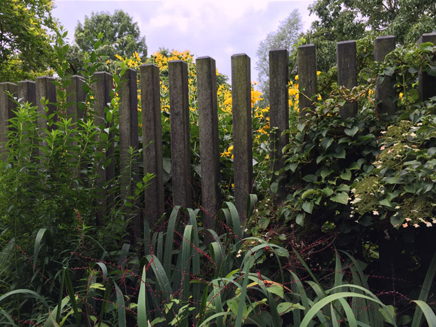 Concrete fence posted spaced to leave negative spaces and a view beyond